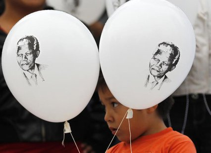 A child holds up balloons with images of former South African President Nelson Mandela as he participates in a celebration to mark Mandela's