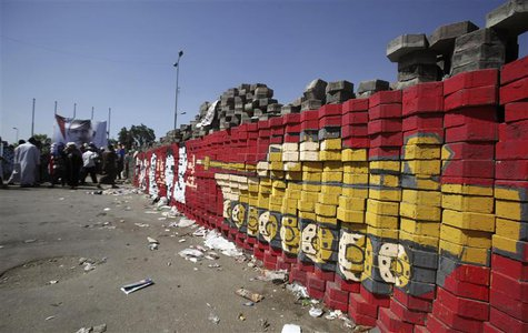 Members of the Muslim Brotherhood and supporters of ousted Egyptian President Mohamed Mursi guard bricks placed at the entrance to their cam