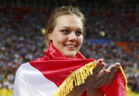 Sandra Perkovic of Croatia holds up her national flag as she celebrates winning the gold medal in the women's discus throw final during the