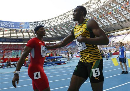 Usain Bolt of Jamaica (R) pushes Mike Rodgers of the U.S. in jest after winning his men's 100 metres semi-final during the IAAF World Athlet