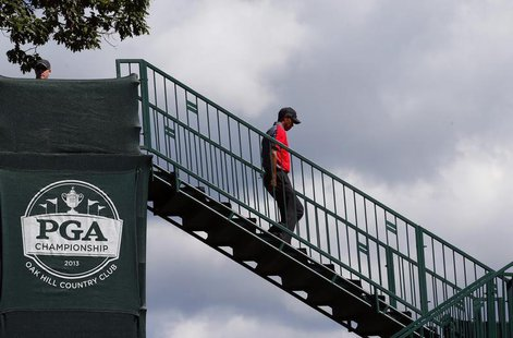 Tiger Woods of the U.S. walks to the first tee during the final round of the 2013 PGA Championship golf tournament at Oak Hill Country Club