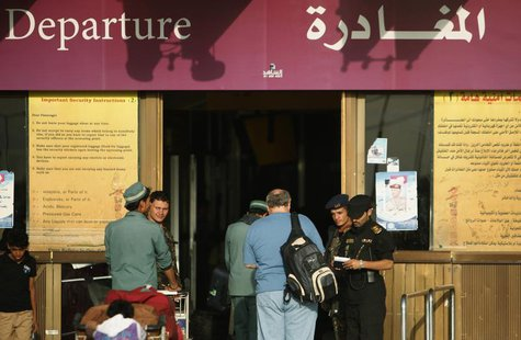 A police officer checks documents of a traveller outside the departure lounge Sanaa International Airport August 7, 2013. REUTERS/Khaled Abd