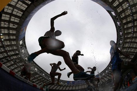 Competitors jump a water obstacle in the men's 3000 metres steeplechase heat during the IAAF World Athletics Championships at the Luzhniki S