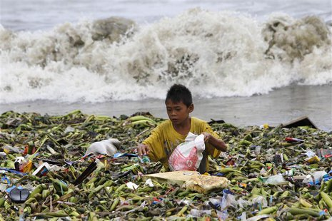 A boy sifts through floating garbage as he collects recyclable items to sell while strong waves crash along the shores of Manila Bay, near a