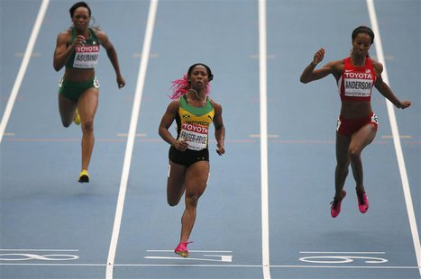 Shelly-Ann Fraser-Pryce of Jamaica (C) crosses the finish line between Gloria Asumnu of Nigeria (L) and Alexandria Anderson of the U.S. (R)