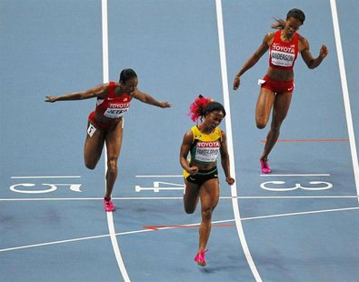 Shelly-Ann Fraser-Pryce of Jamaica (C) celebrates winning the women's 100 metres final next to Carmelita Jeter of the U.S. (L) and Alexandri
