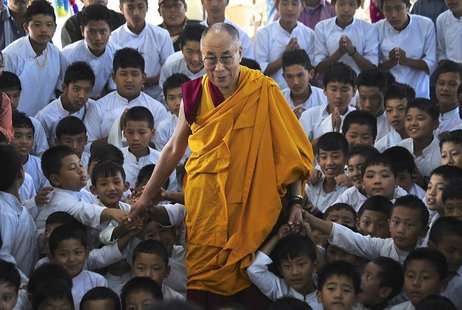 Exiled Tibetan spiritual leader the Dalai Lama poses for a picture with the students of a Tibetan school after inaugurating its auditorium a