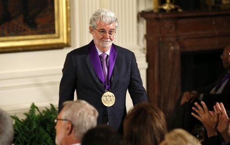 Film producer George Lucas walks to his seat after U.S. President Barack Obama awarded him the 2012 National Medal of Arts during a ceremony
