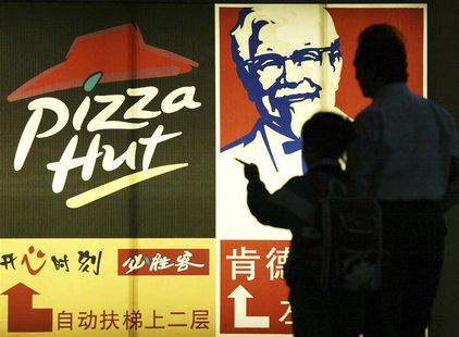 People stand in front of a poster of KFC and Pizza Hut in Guangzhou, capital of south China's Guangdong province April 2, 2007. REUTERS/Joe