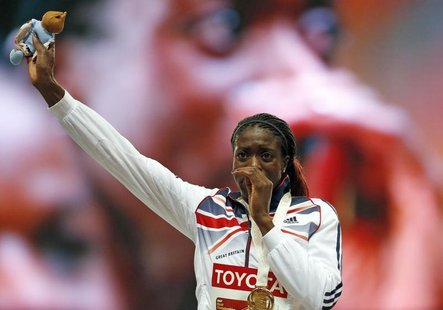 Winner Christine Ohuruogu of Britain reacts on the podium at the victory ceremony for the women's 400 metres final during the IAAF World Ath