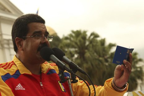 Venezuela's President Nicolas Maduro (C) holds a copy of the Venezuelan constitution as he speaks during a rally in Caracas in this handout