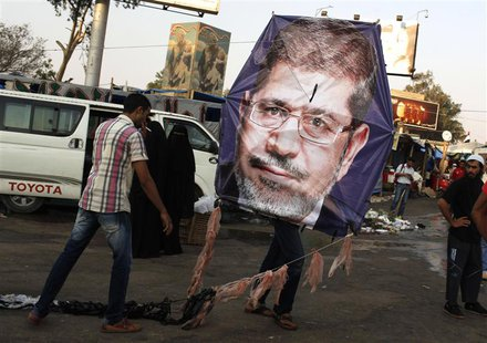 Supporters of deposed Egyptian President Mohamed Mursi fly a kite with a picture of Mursi, in the sit-in area of Rab'a al- Adawiya Square, w
