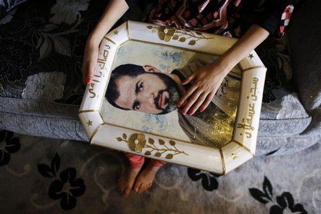 Verde holds a framed portrait of her relative, Palestinian prisoner Jamil Nabi Annatsheh, ahead of his release from an Israeli prison, in th