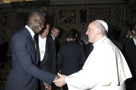 Italian national soccer player Mario Balotelli (L) shakes hands with Pope Francis during a private audience at the Vatican, August 13, 2013.