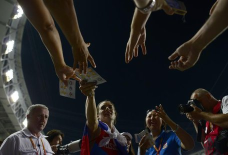 Yelena Isinbayeva of Russia signs autographs after women's pole vault final at the IAAF World Athletics Championships at the Luzhniki stadiu