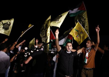Palestinians wave flags and shout as they await the release of prisoners outside the Israeli prison of Ofer, near the West Bank city of Rama