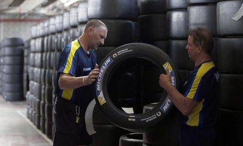 Workers hold a motorsport racing tyre stocked in the Michelin tyre company's factory in Clermont-Ferrand, central France, July 10, 2013. REU