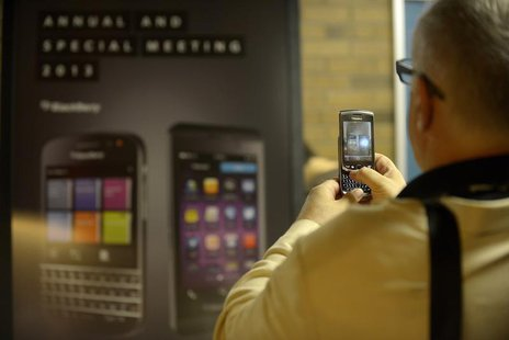 A Blackberry user takes a photograph of Blackberry signage at the company's annual meeting in Waterloo, Ontario July 9, 2013. REUTERS/Jon Bl