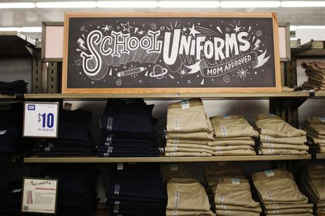 "A stack of school uniforms are seen on the shelves inside the Old Navy clothing shop during a ""ChildSpree"" back-to-school shopping event in"