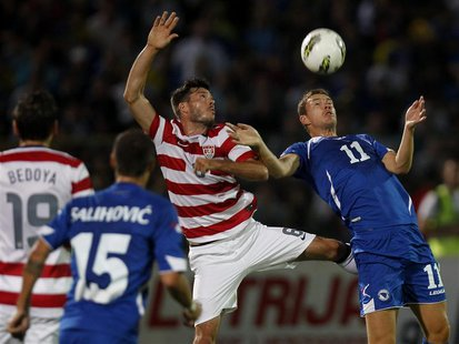 Bosnia's Edin Dzeko (R) fights for the ball against Brad Evans of the U.S. during their international friendly soccer match in Sarajevo, Aug