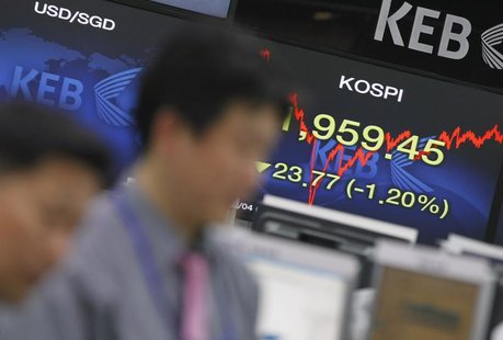 Currency dealers watch a monitor as a screen (R) shows South Korea's main stock market index, KOSPI, at a dealing room of a bank in Seoul Ap