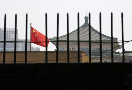 The national flag of China flutters behind a fence of the headquarters of the National Development and Reform Commission (NDRC) in Beijing,