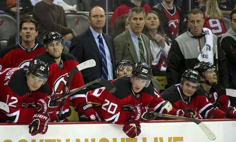 New Jersey Devils head coach Peter DeBoer (back 2nd L) and assistant coach Dave Barr (back 3rd L) stand on the bench with their players as t