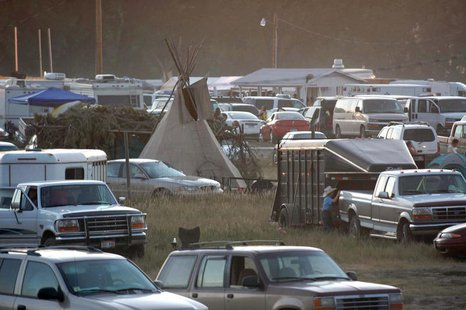 A traditional tipi is surrounded by cars as the parking lot fills up for the Oglala Nation Pow Wow and Rodeo in Pine Ridge, South Dakota, Au