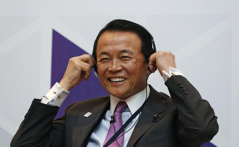 Japan's Finance Minister Taro Aso smiles as he adjusts his headphones during a seminar at the Asian Development Bank's (ADB) 46th annual boa