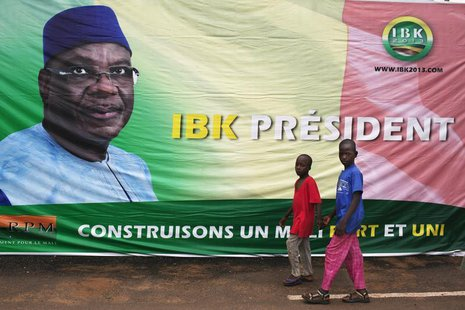 Boys walk in front of a poster of Mali's President-elect Ibrahim Boubacar Keita in Bamako August 13, 2013. REUTERS/Joe Penney