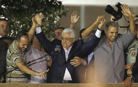 Palestinian President Mahmoud Abbas (C) holds hands with Palestinian prisoners who were released from Israeli prisons during celebrations in
