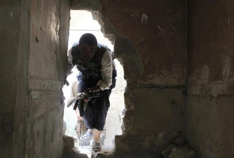 A Free Syrian Army fighter moves through a hole in a wall in the Bab al-Nasr neighborhood of Aleppo August 14, 2013. REUTERS/Melhem Barakat
