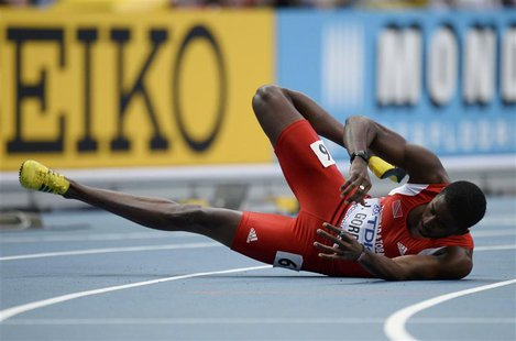 Jehue Gordon of Trinidad And Tobago falls onto the track after crossing the finish line to win the men's 400 metres hurdles final during the