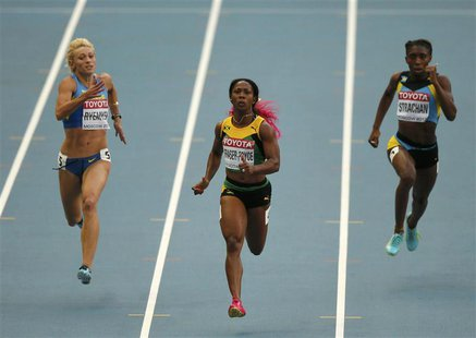 Shelly-Ann Fraser-Pryce of Jamaica (C) runs with Mariya Ryemyen of Ukraine (L) and Anthonique Strachan of Bahamas (R) in their women's 200 m