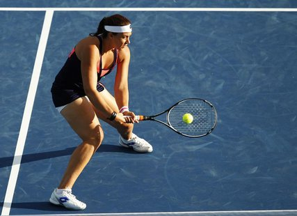 Marion Bartoli of France hits a return to Simona Halep of Romania during their women's singles match at the Cincinnati Open tennis tournamen