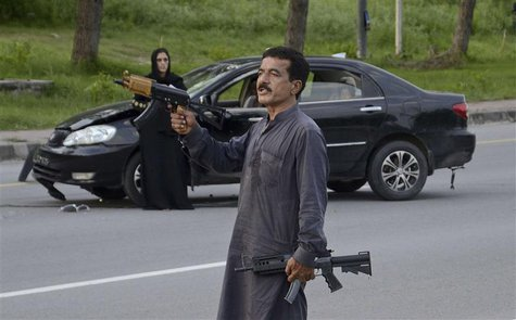 An unidentified man carries arms in Islamabad August 15, 2013. REUTERS/Stringer