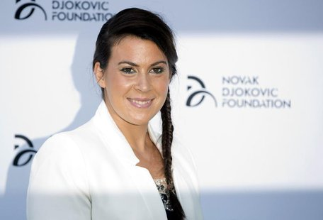 French tennis player Marion Bartoli poses for photographers as she arrives at a fundraising dinner for the Novak Djokovic Foundation in Lond