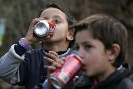 Children of the Kosovo Ashkalli minority drink during a ribbon-cutting ceremony for their new home in the village of Magure in central Kosov
