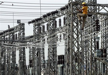 An employee works on electric pylons at a power station in Greater Noida on the outskirts of New Delhi, in this June 8, 2012 file photo. REU