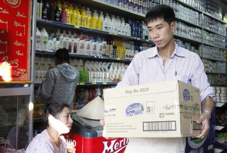 An Abbott Laboratories sales staff carries a carton of powder milk tins out of a shop during a production recall outside Hanoi August 6, 201