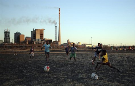Boys play soccer in Marikana's Nkaneng township in front of the Lonmin's Marikana platinum mine in Rustenburg, 100 km (62 miles) northwest o