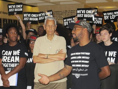 Julian Bond, former NAACP chairman (C), listens as Phillip Agnew, executive director of the Dream Defenders (R), announces an end of a 31-da