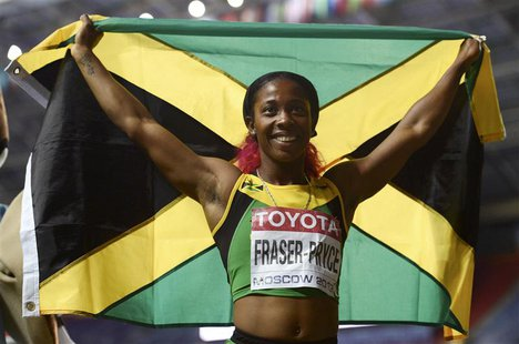 Shelly-Ann Fraser-Pryce of Jamaica holds her national flag as she celebrates winning the women's 200 metres final during the IAAF World Athl