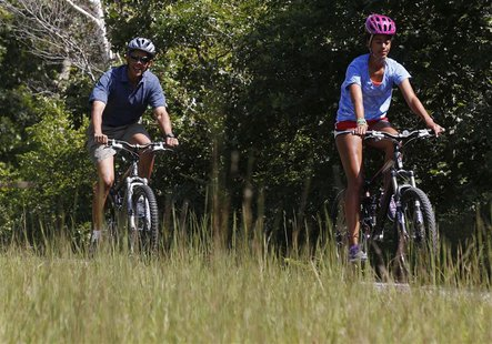 U.S. President Barack Obama (L) bike rides with his oldest daughter, Malia, while at the Manuel F. Correllus State Forest in West Tisbury on