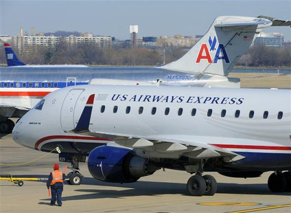 A US Airways Express plane (foreground) departs from a gate past an American Airlines plane (background) at the Ronald Reagan Washington Nat