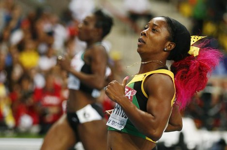 Shelly-Ann Fraser-Pryce of Jamaica runs ahead of Murielle Ahoure of the Ivory Coast (L) to win the women's 200 metres final during the IAAF