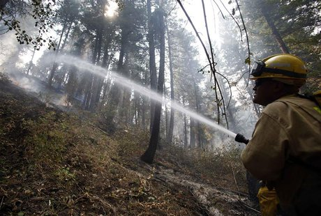 Firefighter Henry Munoz sprays down a hotspot at the Elk Complex wildfire outside Boise, Idaho August 15, 2013. Together with the Elk, Pony,