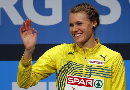 Third placed Emma Green Tregaro of Sweden shows her medal on the podium after the women's High Jump event at the European Athletics Indoor C