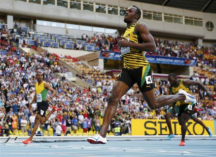 Usain Bolt of Jamaica (R) crosses the finish line to win the men's 200 metres final ahead of teammate Warren Weir (L) during the IAAF World