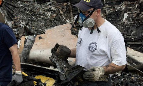 National Transportation Safety Board (NTSB) investigators retrieve the flight voice and data recorders from the wreckage of UPS flight 1354